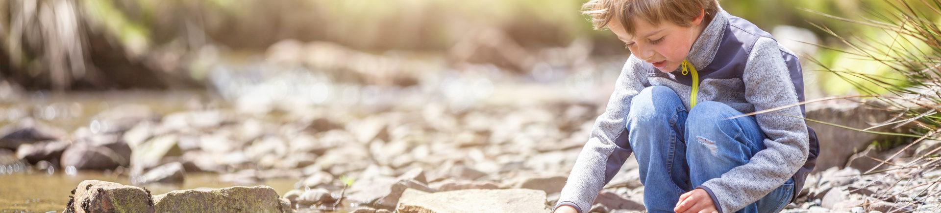 Kind speelt in de zon met een papieren bootje